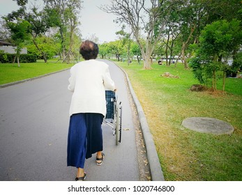 The elderly women are wheeling wheelchair empty at the park