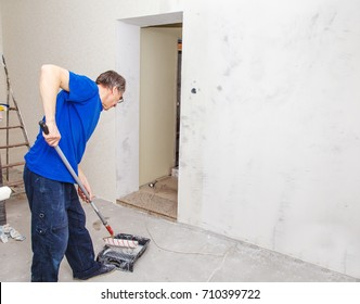 elderly worker painting wall with background glue for a wallpaper