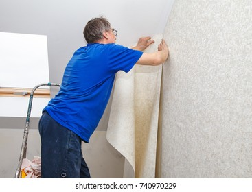 elderly worker smoothing wallpaper in his house