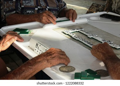 Elderly men's wrinkled and freckled hands shown touching tiles as they play dominoes on a white  in open space in Little Havana, Miami FL