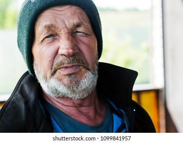 Elderly wrinkled man in a knitted cap close-up portrait