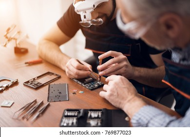 Elderly and young men repair a mobile phone together. They work in a repair shop. They use different tools. They are repair specialists.