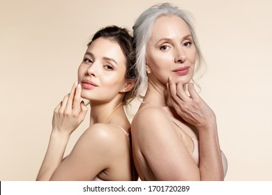 Elderly and young women with smooth skin and natural makeup standing back-to-back. Thinking, planning, dreaming