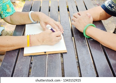 Elderly's female hand writing in white notebook, learning on dark brown plank wooden table in the park, crop picture in vintage tone with shadow light of sunny, never too late for learn concept