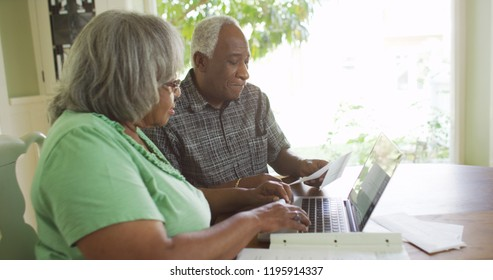 Eldery black man looking at bills with wife