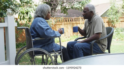 Eldery black woman in wheelchair talking with husband