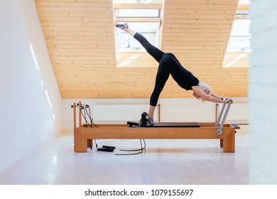 Eldery blond woman in black sportswear professional instructor pilates practicing stretching exercise on reformer in gym.