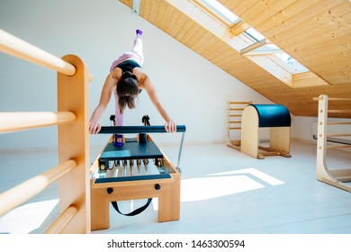Eldery blond woman in black top sportswear professional instructor pilates practicing stretching exercise on reformer in pilates studio, working out indoor, special equipment on foreground.