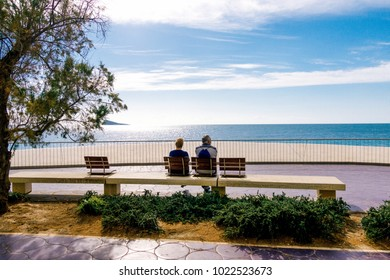 Eldery couple relax sitting on the bench and looking to the sea in Benidorm, Spain