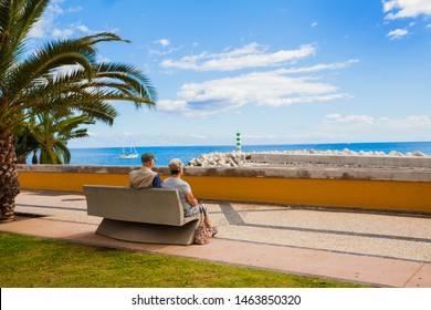 Eldery couple is resting on vacation, relaxing under the palm tree and looking towards Atlantic ocean on holidays in Funchal Madeira Portugal in sunny day