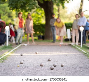 Eldery friends playing petanque in city park woman throwing a ball outdoor summer activity