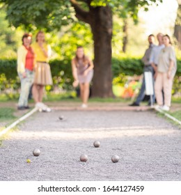 Eldery friends playing petanque woman throwing a ball outdoor summer city park