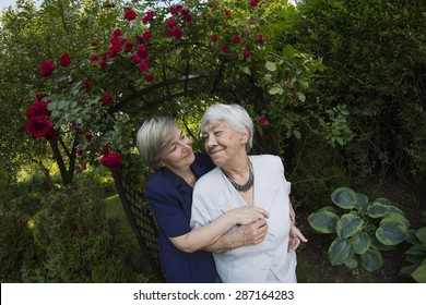 Eldery, gray woman with her daughter in garden
