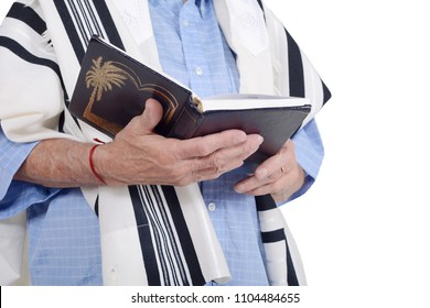 Eldery jewish man with kippah and wrapped in talit praying with siddur. Religion concept