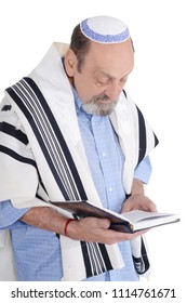 Eldery jewish man with kippah and wrapped in talit praying with siddur. Religion concept. Isolated white background