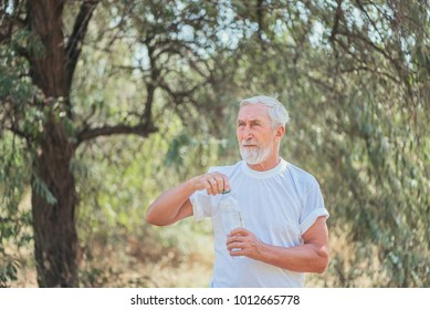 Eldery man with grey hair and beard in white shirt opening a bottle of water in the park for a walk, the concept of an active lifestyle in old age