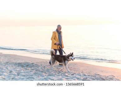 Eldery mancwith grey hair and beard in a yellow raincoat with husky dog walking along sea on the beach at sunrise
