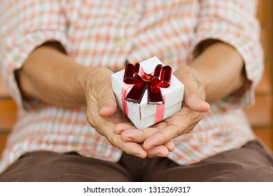 Eldery person hold a gift box in hand. Concept of Support, help, nursing home or help for elderly