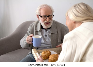 Eldery woman bringing her husband morning meal. Aged lady giving her husband some coffee and croissants for breakfast in their apartment.