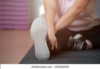 Eldery woman is engaged in stretching on a sports rug. Healthy lifestyle and healthy legs concept