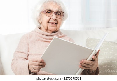 Eldery woman looking photos in white photo album