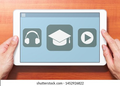 E-learning concept image. Closeup of hands touching white tablet computer on wooden desk. Application on screen. Front view image.