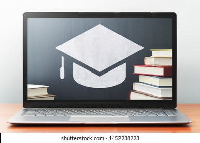 E-learning concept image. Laptop computer on wooden desk.  Book, bachelor's cap icon and blackboard. Front view image.