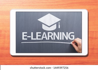 E-learning concept. Tablet computer on wooden desk. Teacher writing on blackboard. Front view image.