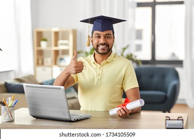 e-learning, education and people concept - happy smiling indian male graduate student with laptop computer and diploma showing thumbs up at home