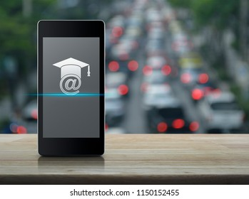 E-learning flat icon on modern smart mobile phone screen on wooden table over blur of rush hour with cars and road, Business study online concept