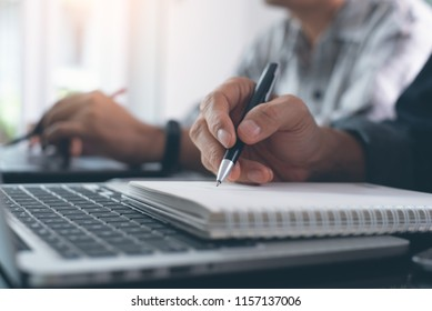 Elearning, online working concept. Business man working on laptop computer, searching and taking note on paper notebook with pen. Students attending course online class