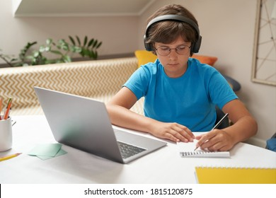 E-learning. Smart little boy in headphones using laptop while studying online, sitting at the table in his room