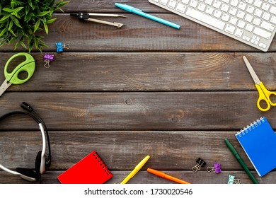 E-learning. Stationery, headphones and keyboard on wooden table top-down frame copy space