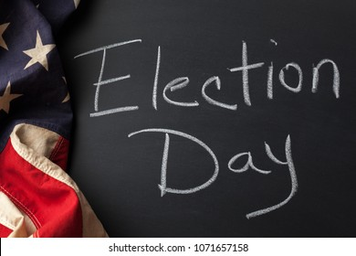Election Day sign handwritten on a chalkboard bordered by a vintage American flag