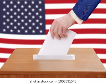 Election Day in the United States of America. A person votes by throwing a ballot in the ballot box