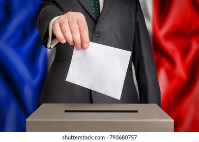 Election in France - voting at the ballot box. The hand of man putting his vote in the ballot box. Flag of  on background.