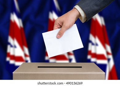 Election in Great Britain. The hand of man putting his vote in the ballot box. British flags on background.