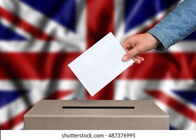 Election in Great Britain. The hand of woman putting her vote in the ballot box. British flag on background.