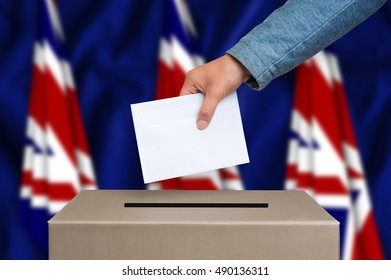 Election in Great Britain. The hand of woman putting her vote in the ballot box. British flags on background.