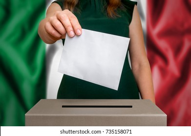 Election in Italy - voting at the ballot box. The hand of woman putting her vote in the ballot box. Flag of Italy on background.