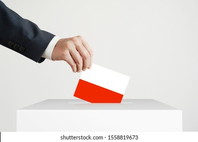 Election. Man putting a ballot with Polish flag into a voting box.