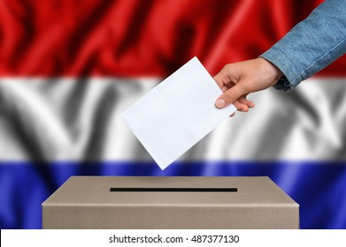 Election in Netherlands. The hand of woman putting her vote in the ballot box. Dutch flag on background.
