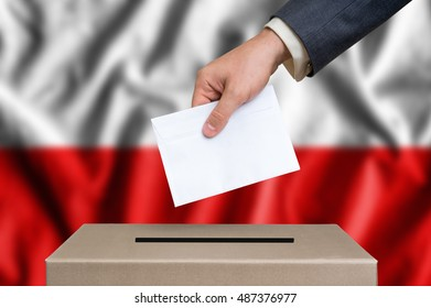 Election in Poland. The hand of man putting his vote in the ballot box. Polish flag on background.