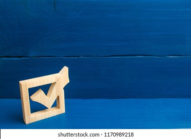 Election of the President or Government. Democracy, development, civil initiative. A wooden checkmark in the box on a blue background. The concept of suffrage, voting in elections.