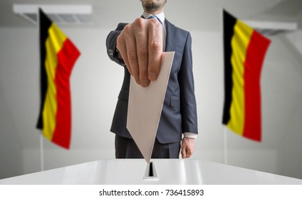 Election or referendum in Belgium. Voter holds envelope in hand above ballot. Belgian flags in background.