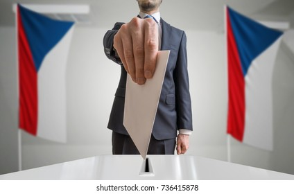 Election or referendum in Czech Republic. Voter holds envelope in hand above ballot. Czech flags in background.
