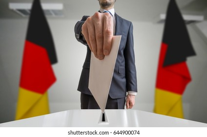 Election or referendum in Germany. Voter holds envelope in hand above ballot. German flags in background.