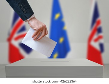 Election or referendum in Great Britain. Voter holds envelope in hand above vote ballot. British and European Union flags in background.