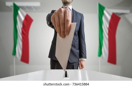 Election or referendum in Italy. Voter holds envelope in hand above ballot. Italian flags in background.