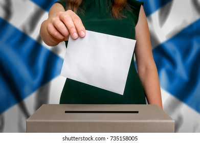 Election in Scotland - voting at the ballot box. The hand of woman putting her vote in the ballot box. Flag of Scotland on background.